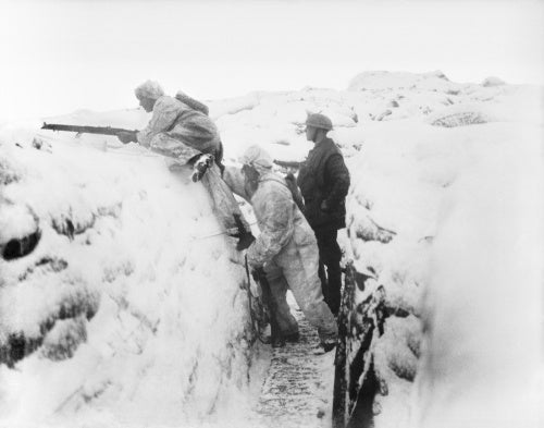 Two men of the 12th East Yorkshires wearing snow suits leaving their snow-covered trench on daylight patrol. Arleux Sector, 9 January 1918.