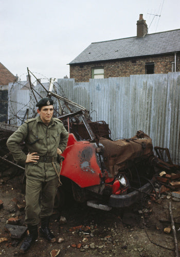 2nd Lieutenant Jonathan Clarke, 1st Royal Green Jackets, with the wreckage of a burnt out car in Belfast, December 1969.