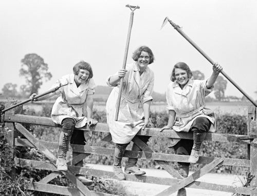 Members of the Women's Land Army climbing over a gate on a British farm during the First World War.