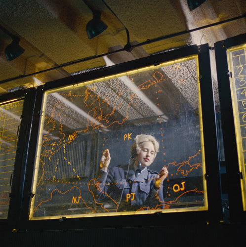 A member of the Women's Royal Air Force at a plotting board at an RAF station, circa 1960.