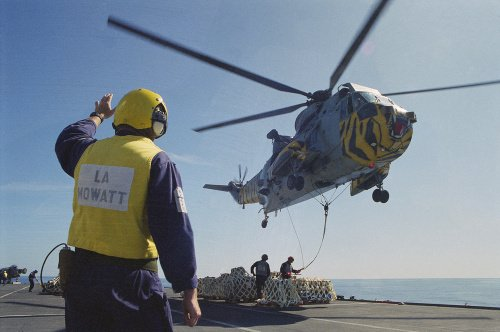 A Westland Sea King of No. 814 Naval Air Squadron picking up stores from HMS INVINCIBLE, 1997.