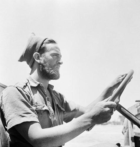 The Western Desert 1942: Head and shoulders portrait of a bearded member of the Long Range Desert Group wearing a woolly cap at the wheel of his jeep.