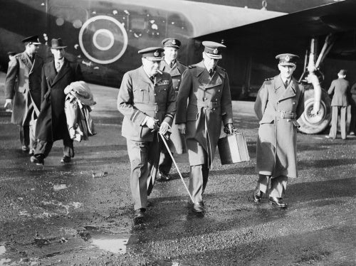 The Prime Minister, Winston Churchill in RAF uniform, accompanied by Air Chief Marshal Sir Charles Portal, Chief of the Air Staff, leaving Consolidated Liberator