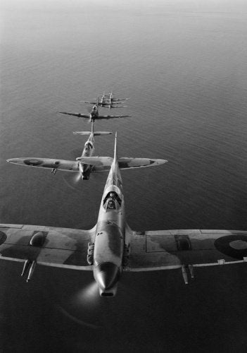 Supermarine Spitfire Mark VCs of No. 2 Squadron SAAF based at Palata, Italy, flying in loose line astern formation over the Adriatic Sea while on a bombing mission to the Sangro River battlefront.