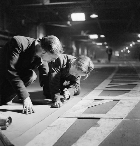 Two men cutting templates in the mould loft.
