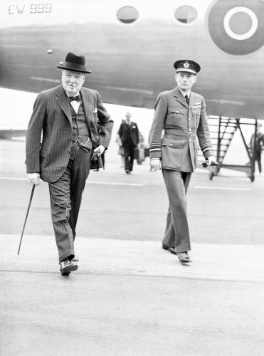 Winston Churchill, accompanied by Air Marshal the Hon. Sir Ralph Cochrane, Air Officer Commanding in Chief, Transport Command, walks from his Douglas Skymaster Mark I, EW999, at Northolt, Middlesex.