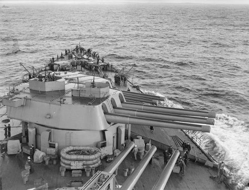 A very clear shot of B turret on board HMS RODNEY taken from the bridge as the ship prepares to enter harbour. Beyond, on the focsle, some of the men are preparing to haul in the paravanes and get the cable cleared for anchoring.