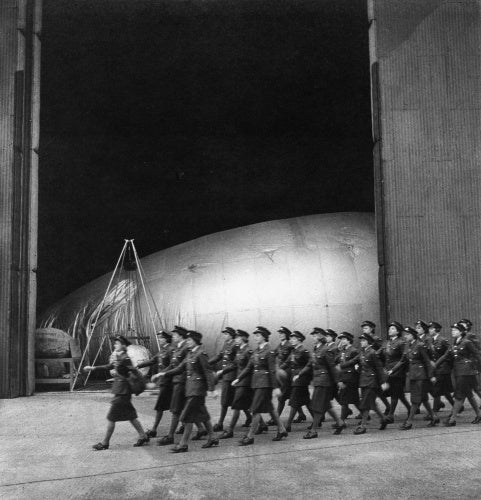 A company of WAAFs marches past a barrage balloon maintenance hangar, RAF Cardington, Bedfordshire, 1941