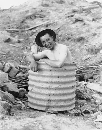 A Canadian soldier keeping cool in a home made tub in the shelling area.