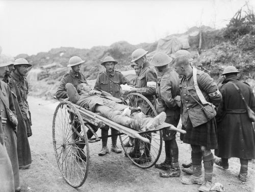 Battle of Bazentin Ridge. An intelligence officer questioning a wounded German prisoner on a stretcher near Contalmaison, Somme, July 1916.