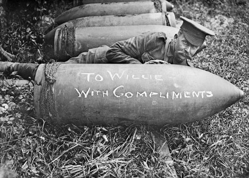 Gunner of the Royal Marine Artillery posing with shell near Acheux, Somme, July 1916.