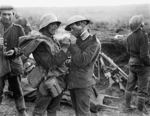 British and German wounded at an advanced dressing station near Epehy share a cigarette, 18 September 1918.