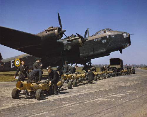 Royal Air Force armourers check over the sixteen 250lb bombs before they are loaded into Short Stirling bomber N6101
