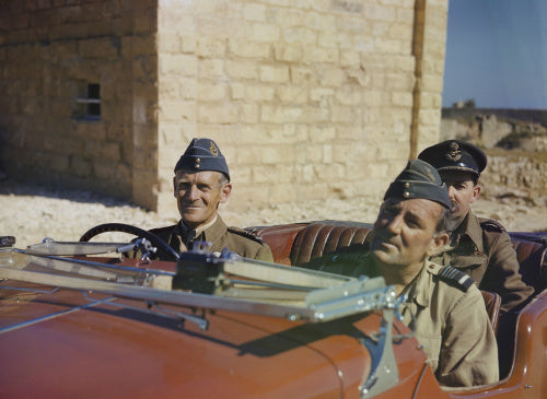 A red MG sports car with Air Vice Marshal Keith Park,  at the wheel and Air Vice Marshal Arthur Coningham