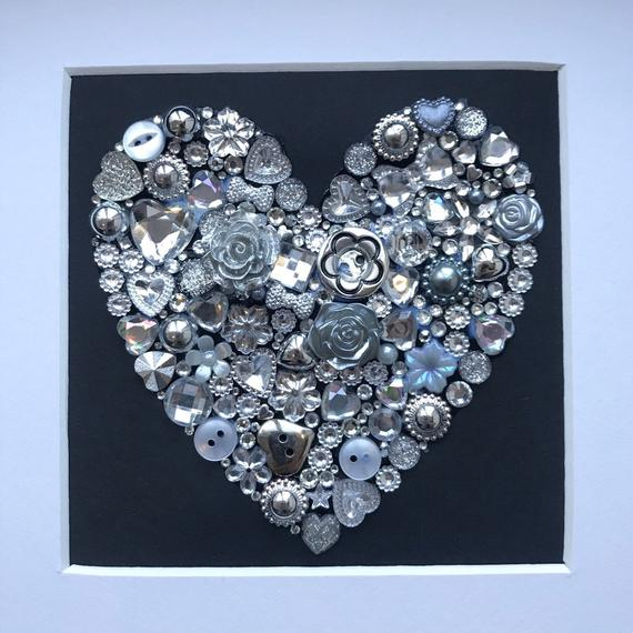 silver sparkly heart button art on black background. Framed picture.