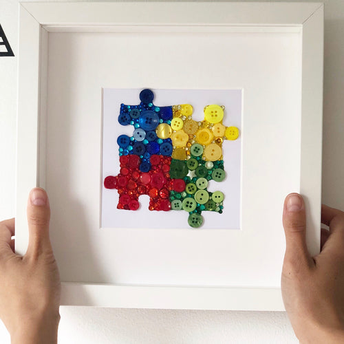 Autism Awareness puzzle piece button art. Framed picture.