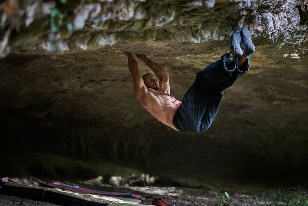 Ripped athlete climbing a massive overhang.