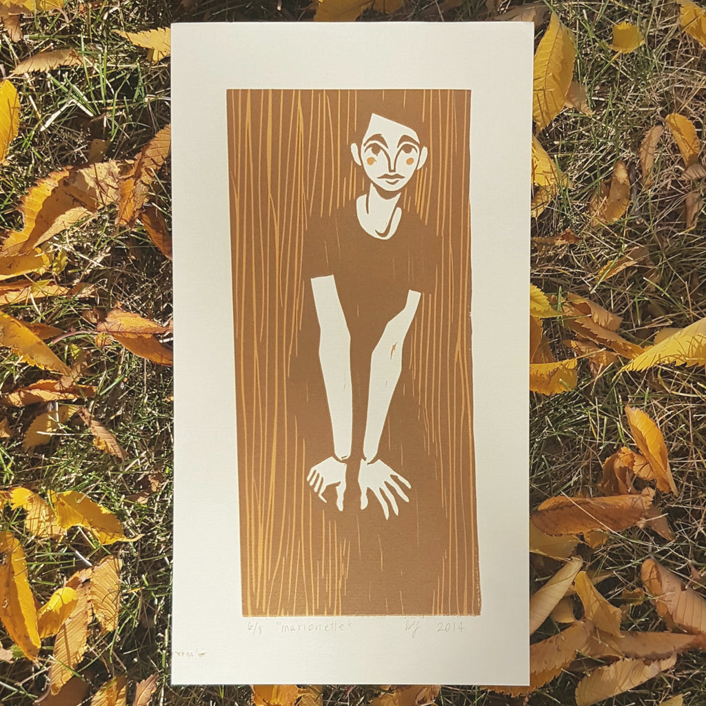 photograph of a print on a pile of yellow fall leaves. the print is a brown and caramel image of an androgynous figure leaning over with their hands on thir knees. it has a folk-type aesthetic with basic shapes and quick lines