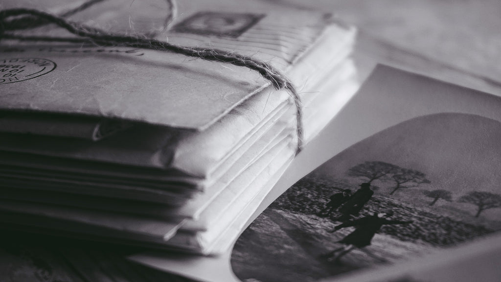 stack of letters tied with twine, an old, oval framed black and white photo of a skaterbeside
