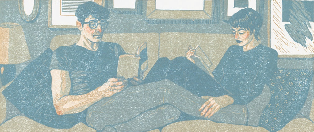 Quarantine Romance: a linocut print in gray and blue of two people reading on a couch.