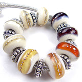Example showing various shades of amber brown and ivory large hole lampwork beads wrapped in fine silver