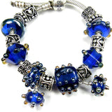 Example group showing cobalt large hole lampwork bead and charm along with other similar colors and styles