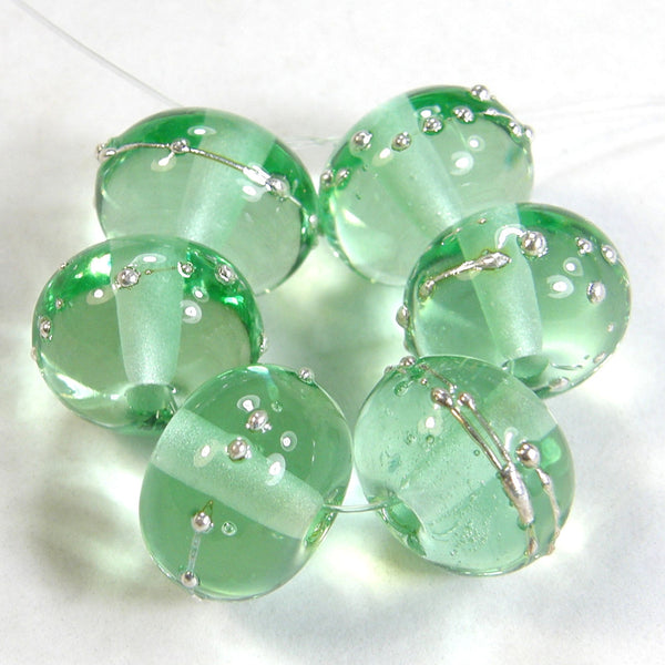 Example of shiny pale green lampwork beads wrapped in fine silver to show color of bead.