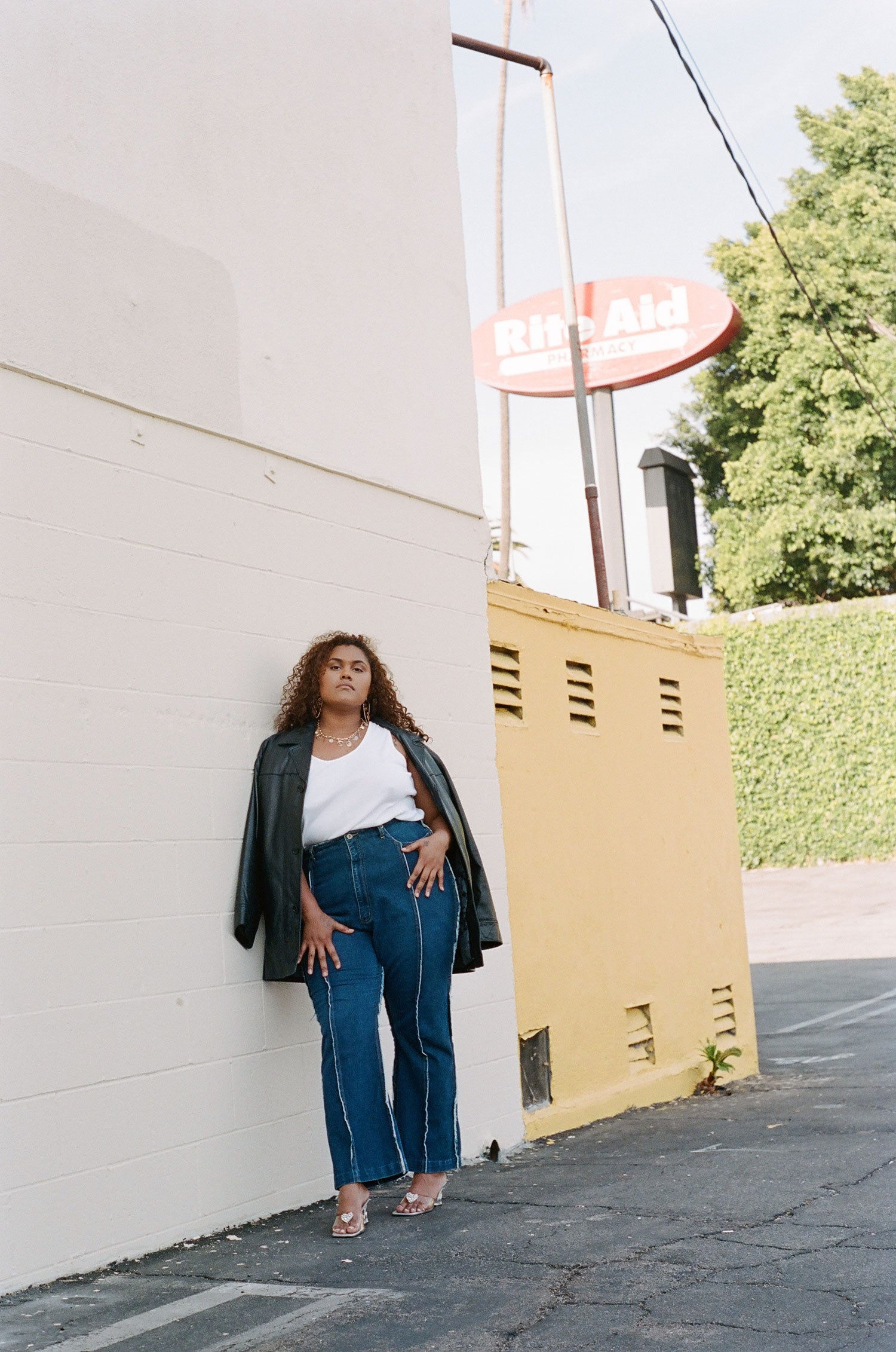 Fashion model leans against wall while wearing plus size vintage leather trench coat, with high waisted 90s jeans