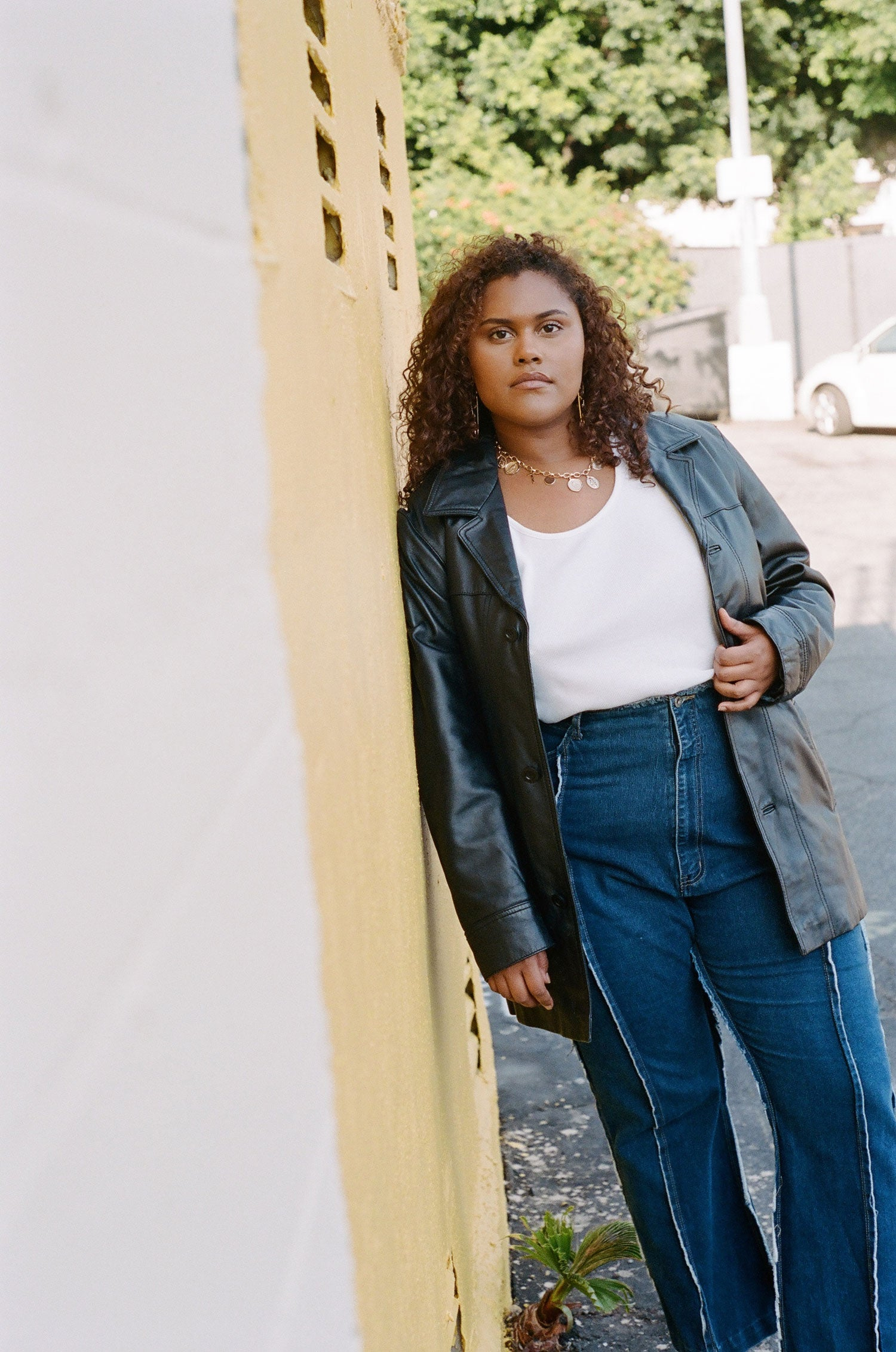 Fashion model leans against wall while wearing vintage 90s leather trench coat and plus size high waisted jeans.