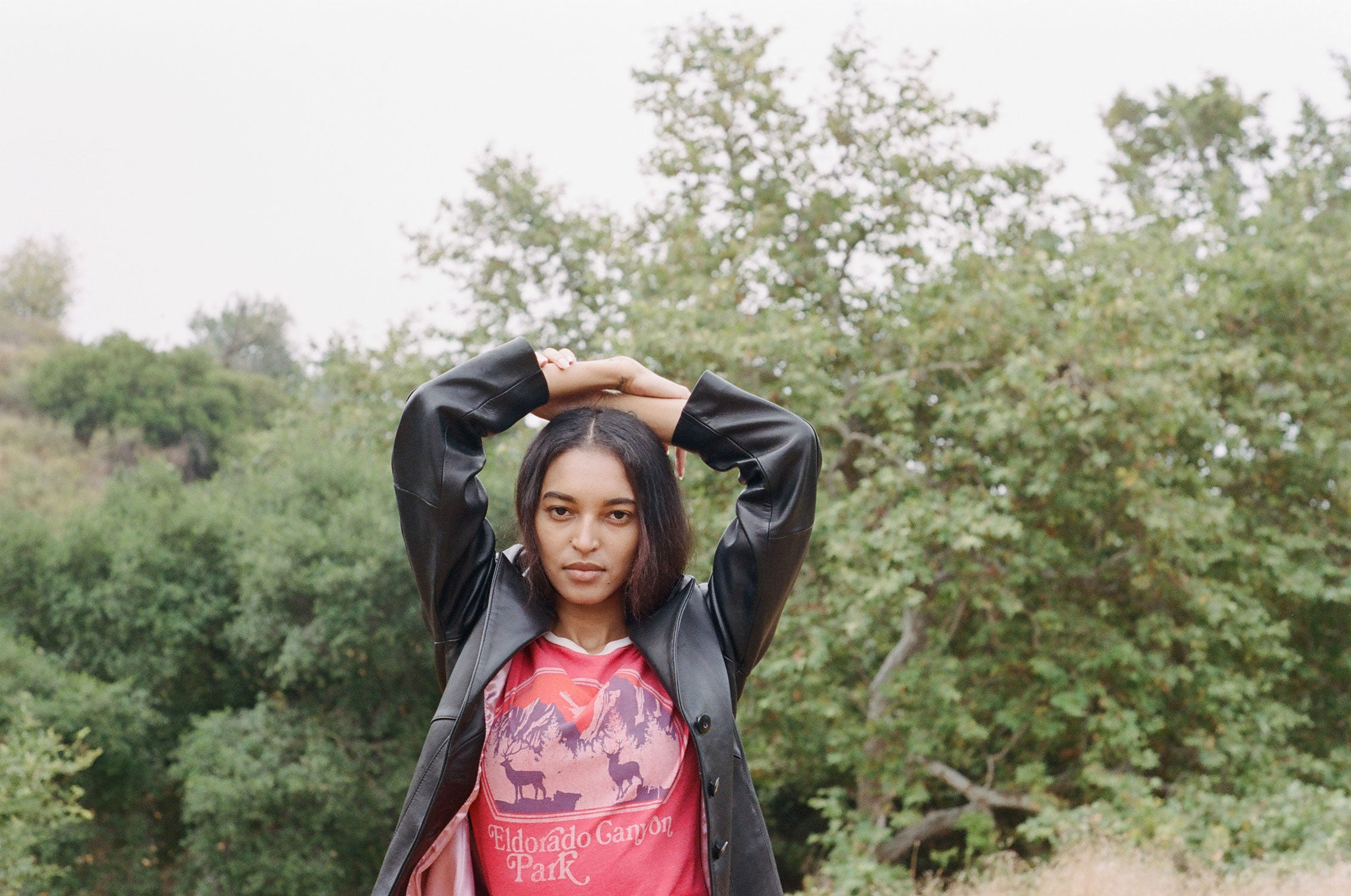 Woman wears grungy 90s leather trench coat with red t shirt in front of mountain scenery