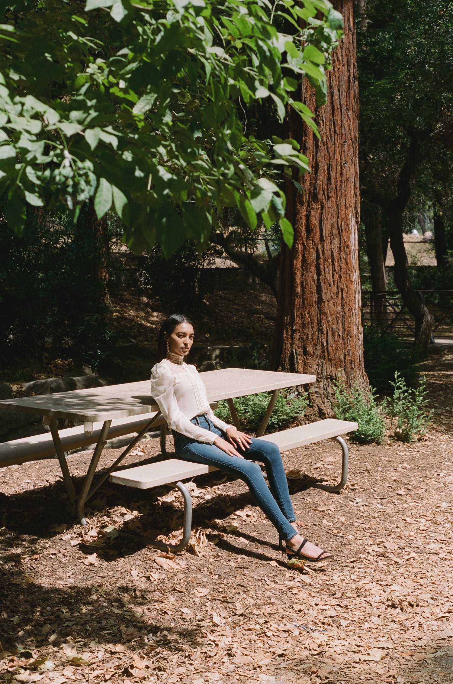 Forest scene with woman on picnic bench wearing vintage 70s Gunne Sax blouse with high waisted Levi's jeans