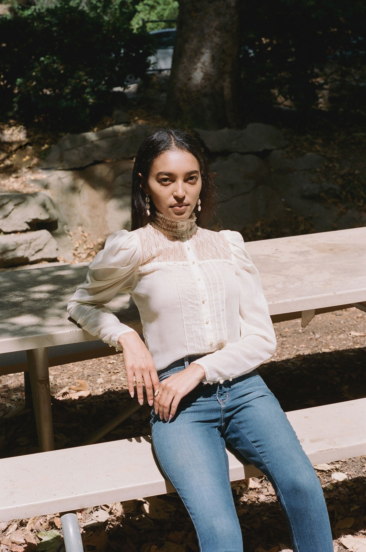 Fashion model sits on picnic table in the sun, wearing vintage 1970s Gunne Sax prairie blouse