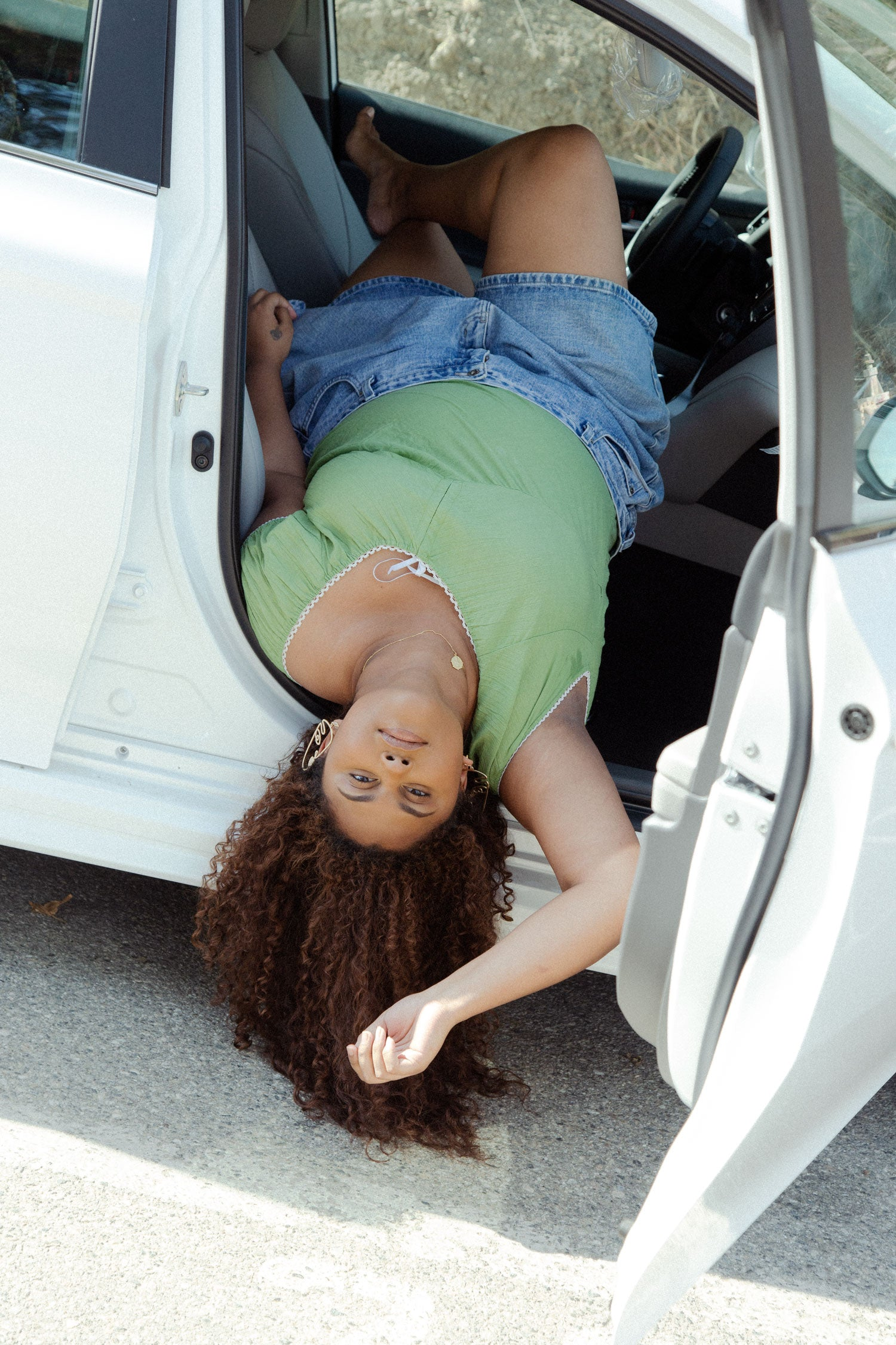 Fashion model hangs upside down out of of car wearing vintage plus size 1990s top and high waisted jeans shorts