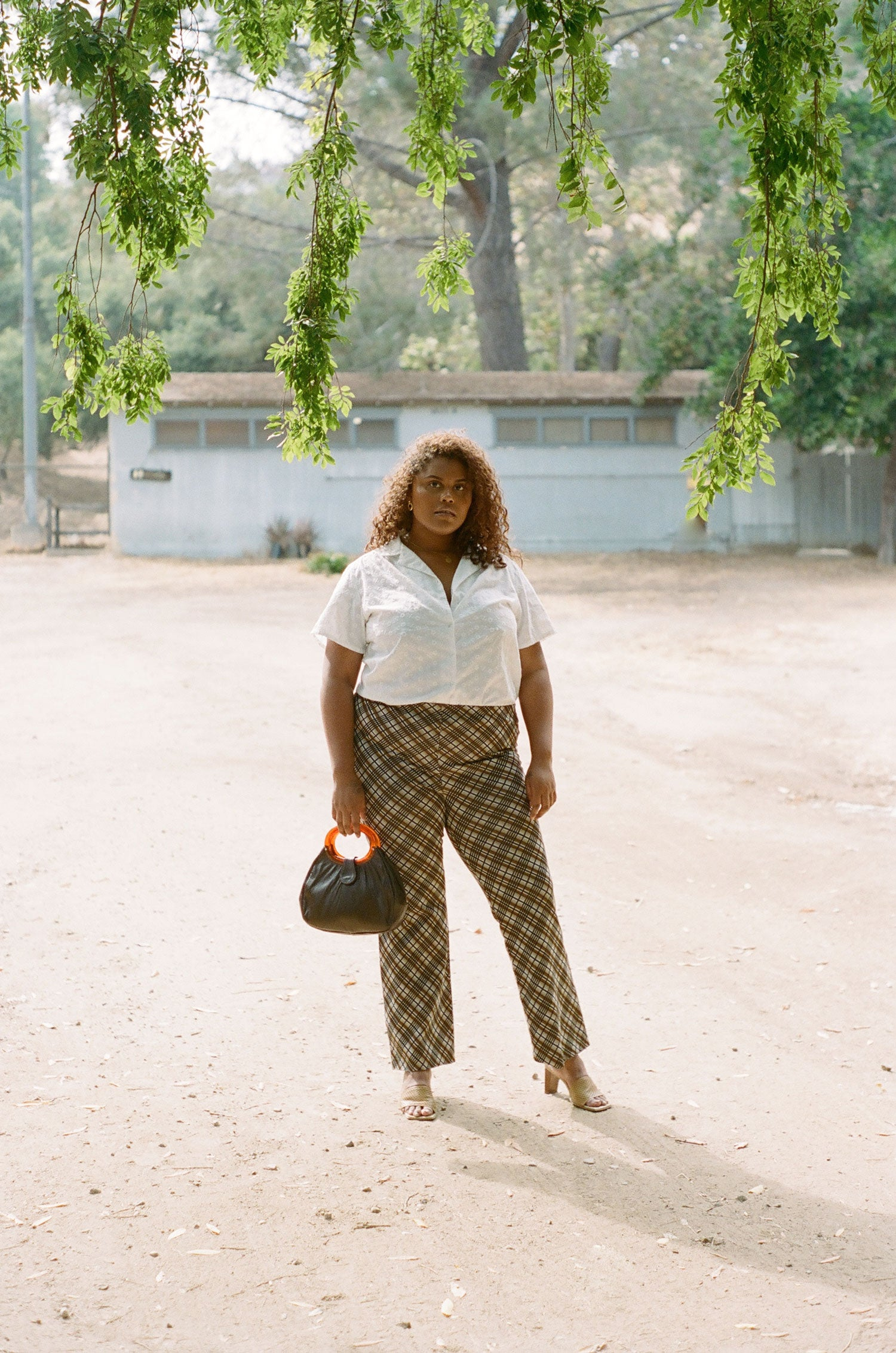 Fashion model stands under willow tree, wearing vintage, plus size, 70s pants and holding mod purse
