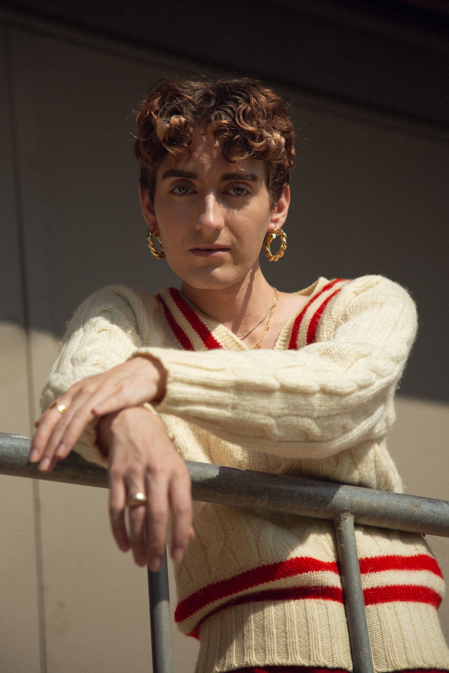 Trans femme model leaning over fence, wearing vintage 70s v neck sweater and red a-line skirt.