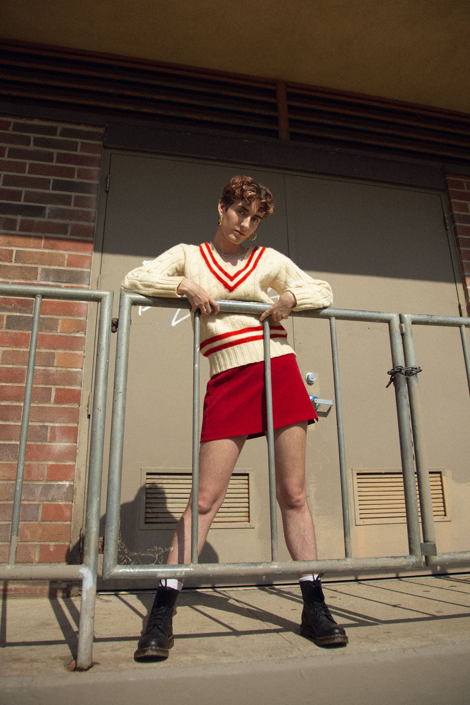 Trans femme model standing behind fence, wearing vintage 70s v neck sweater and red a-line skirt.