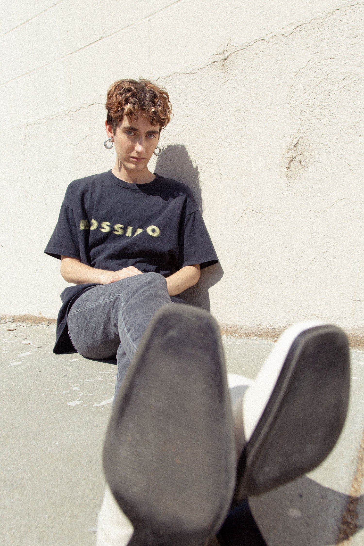 Non binary trans model sits on sidewalk with white boots facing camera. Wearing 90s graphic t shirt and vintage Levi's jeans.