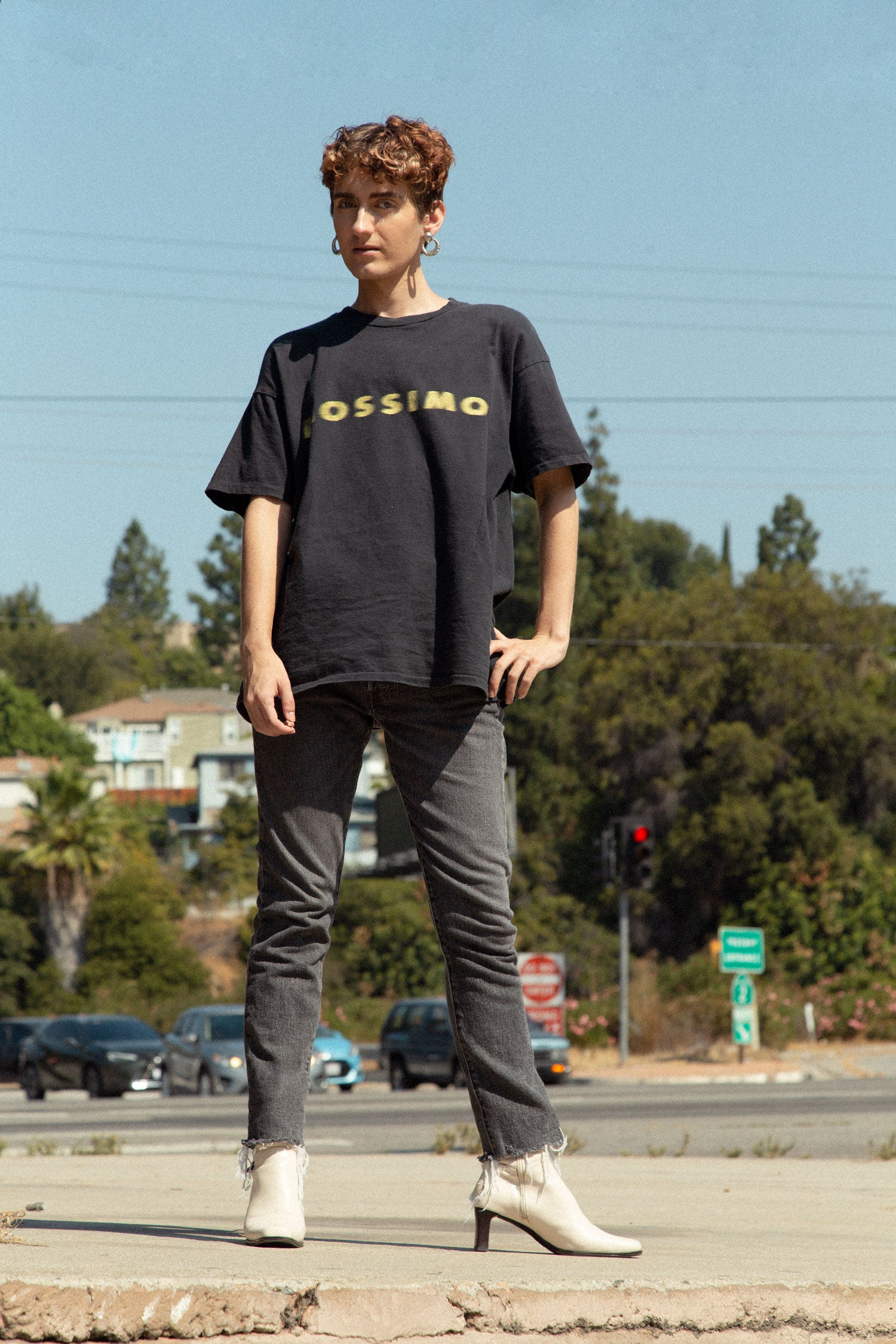Non binary trans model stands in front of road, wearing 90s graphic t shirt, vintage Levi's jeans and white boots.