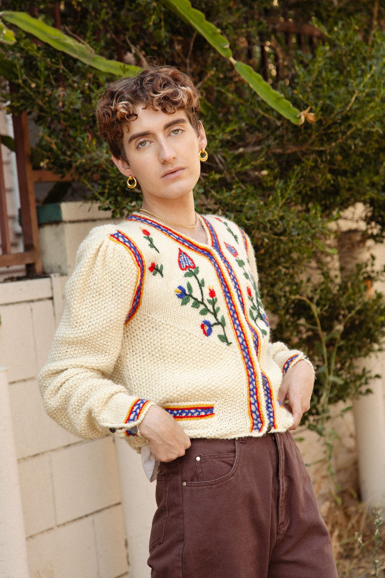 Non binary model wearing vintage chunky knit sweater.  Standing in front of cactus and other greenery.
