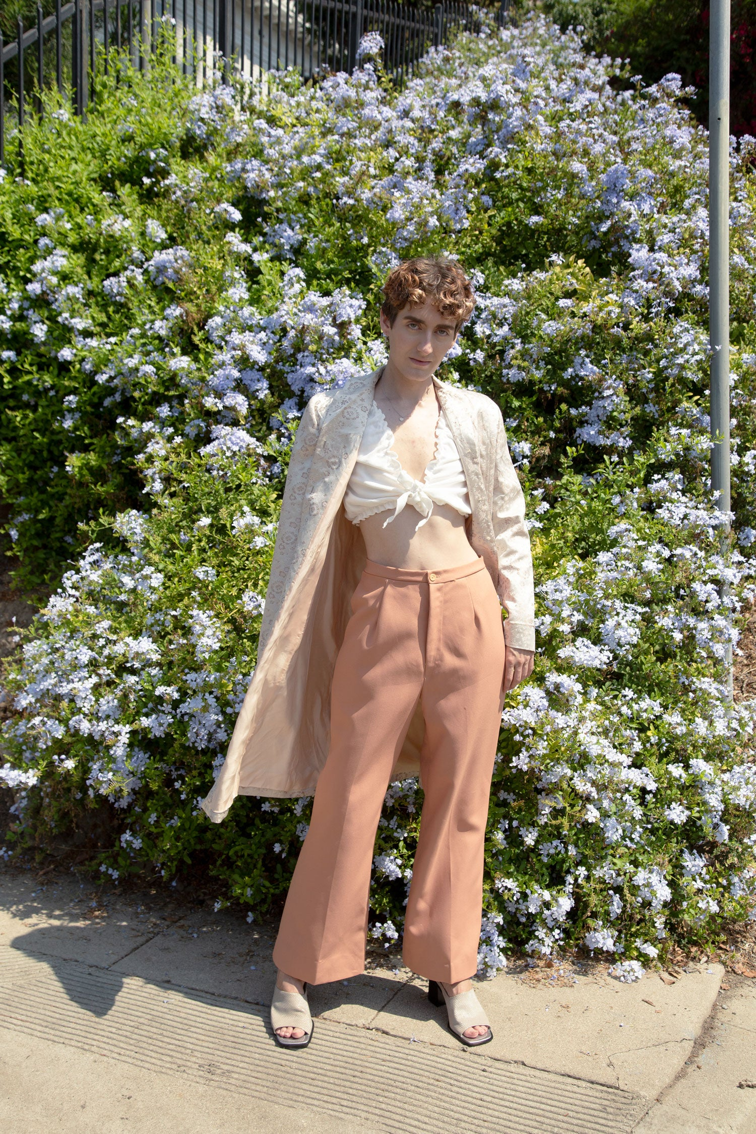 Non binary femme model wearing 90s long jacket, and 70s wide leg pants.  Stands in front of purple flower bush.