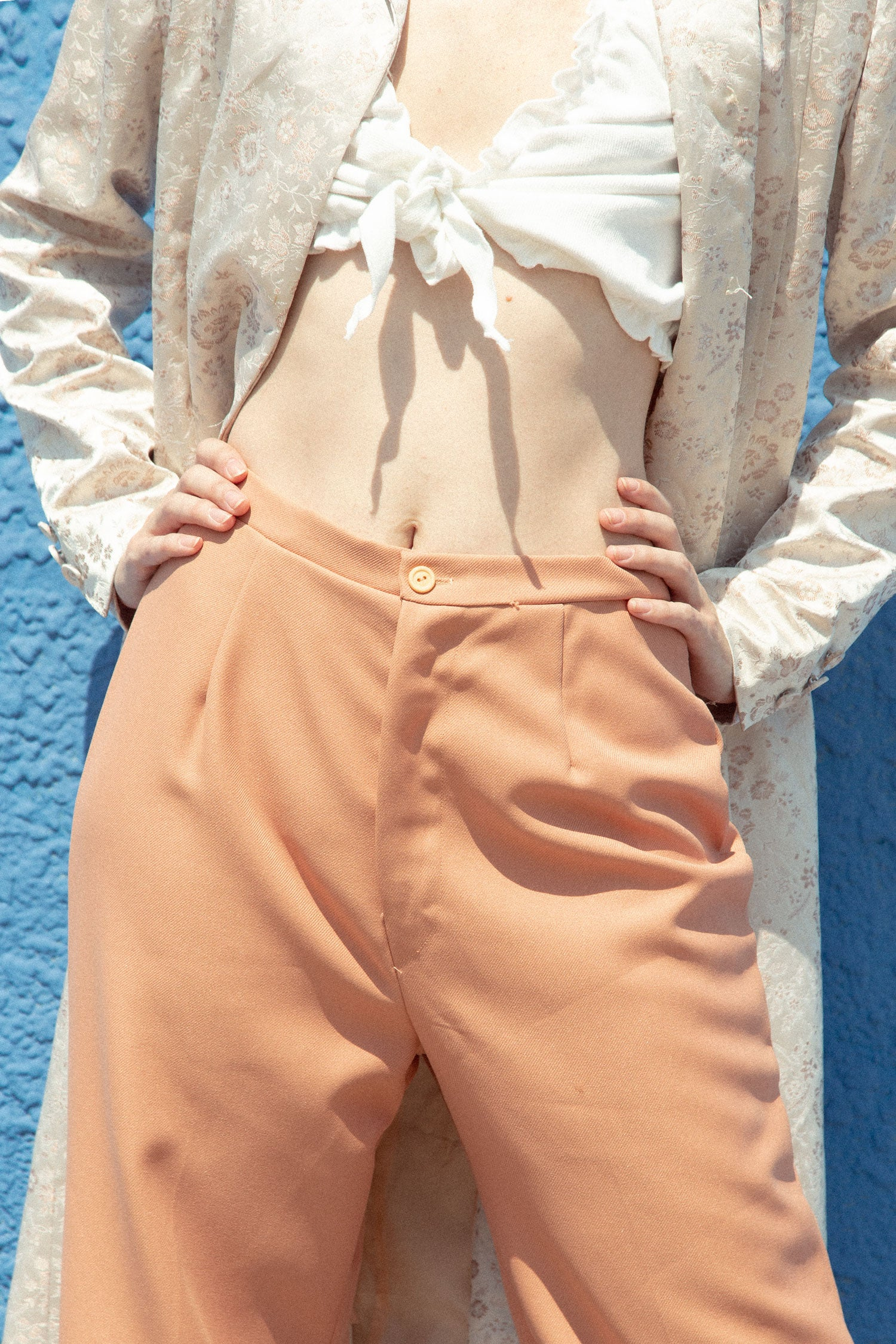Close up photo of non binary femme model wearing 90s long jacket, and 70s wide leg pants.  Standing against blue wall.