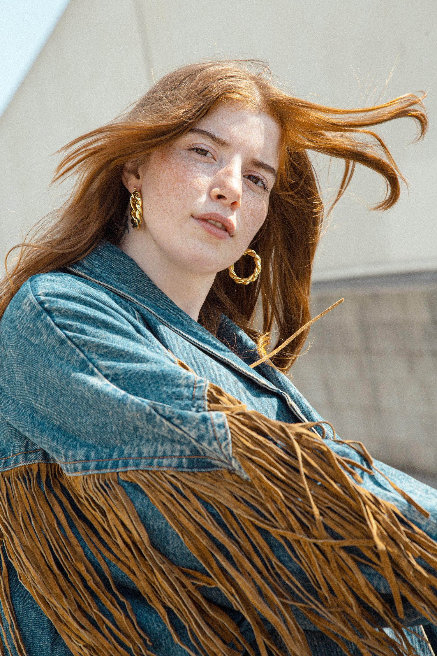Close up of woman wearing vintage denim jacket, with suede fringe.
