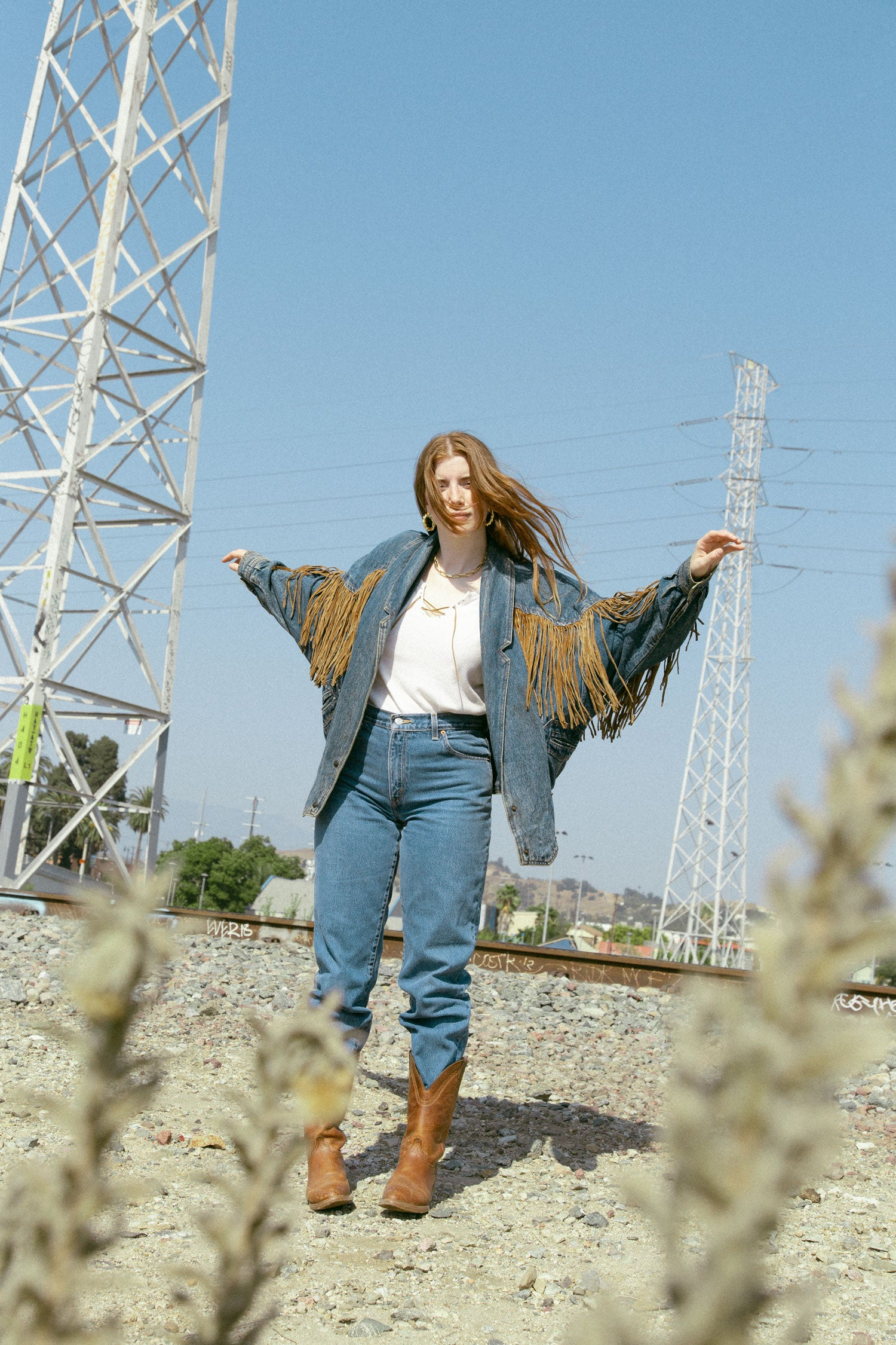 Woman in vintage 90s fringe jacket and high waisted levi's, standing in front of train tracks