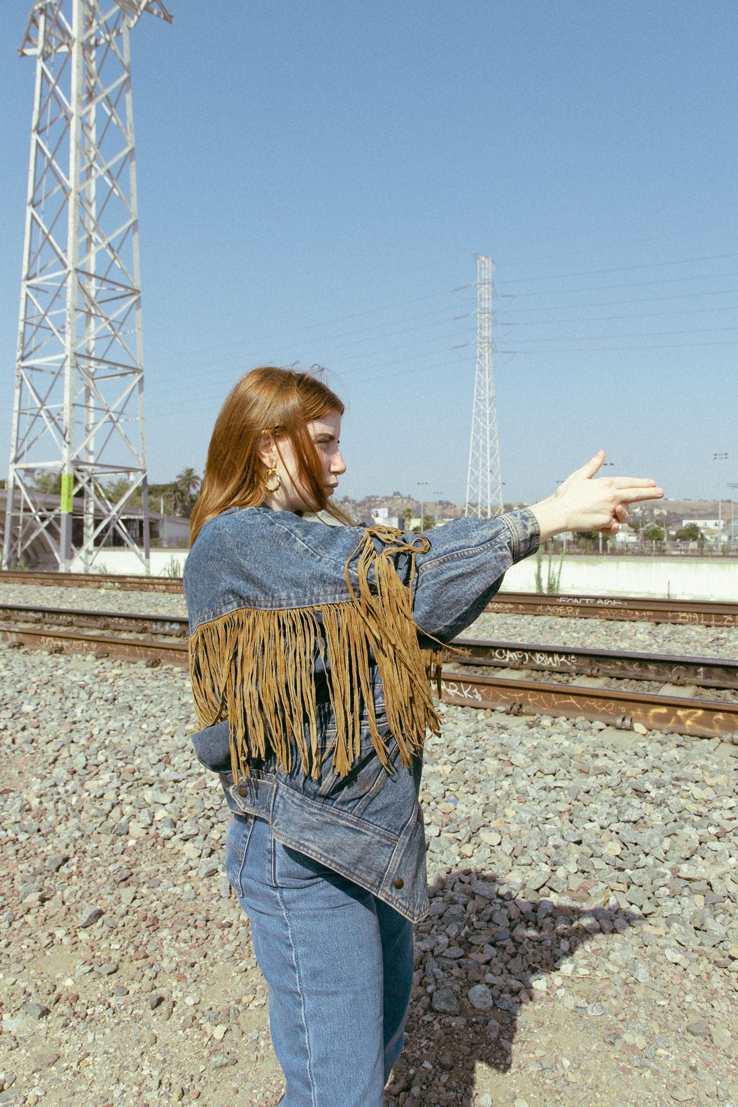 Woman making a hand gun sign in front of train tracks.  Wearing vintage 90s jean jacket with suede fringe.