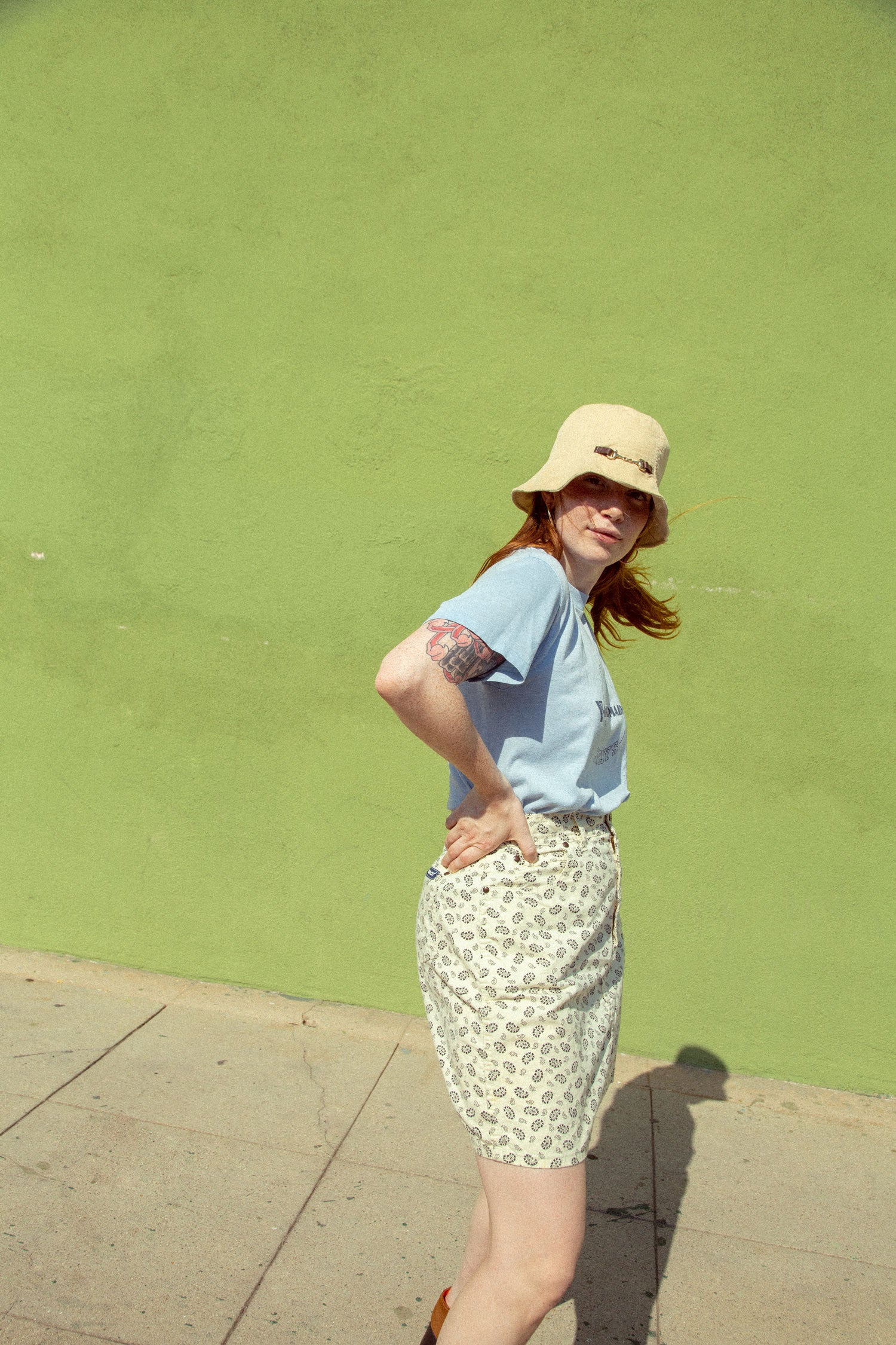 Model wearing 70s vintage YMCA shirt, and paisley skirt.  In front of green wall with wind blowing.