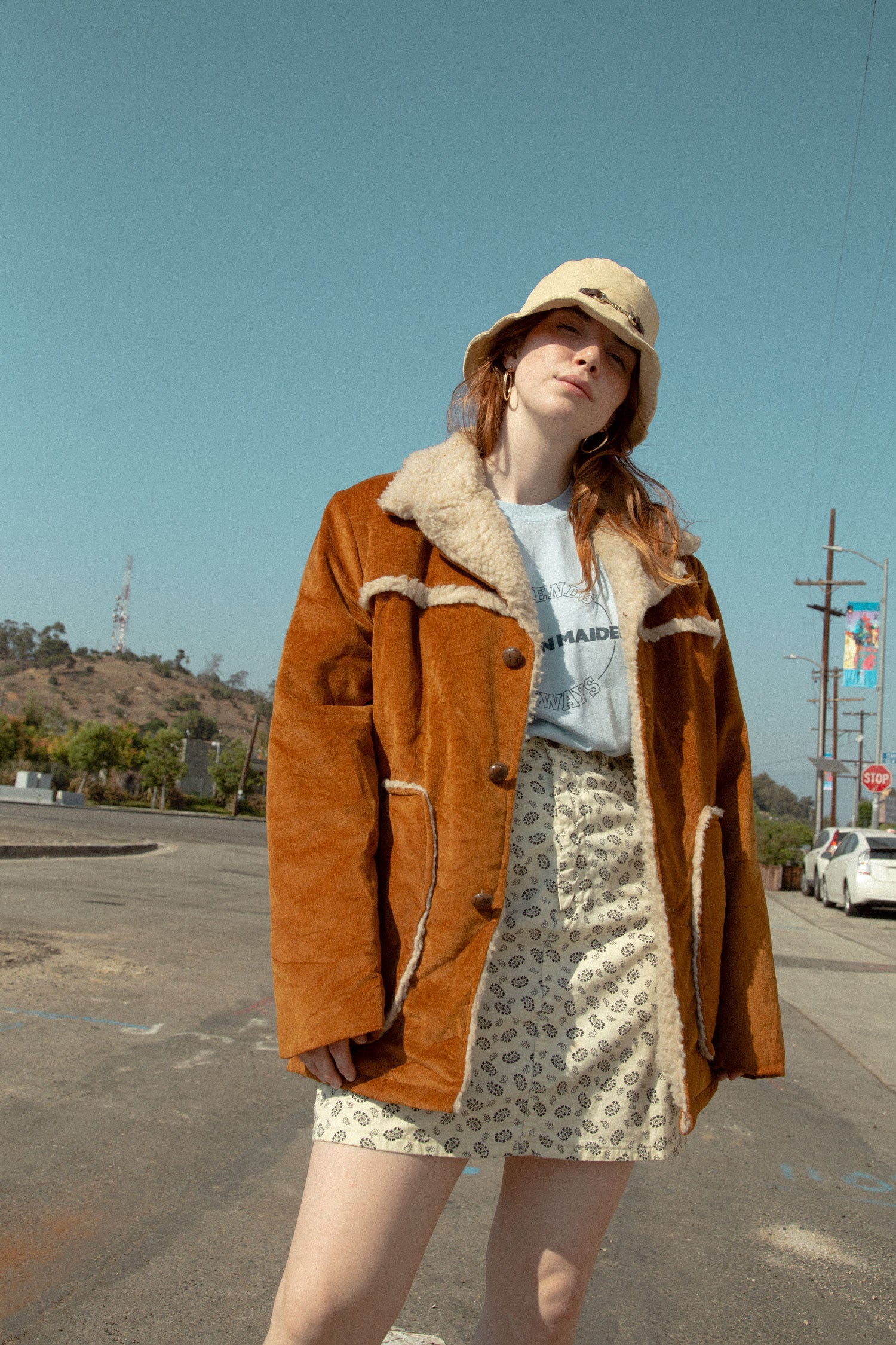 Model wearing vintage bucket hat, 90s fur lined corduroy jacket, 70s single stitch YMCA shirt, and paisley skirt.  Standing in the road, in front of blue sky.
