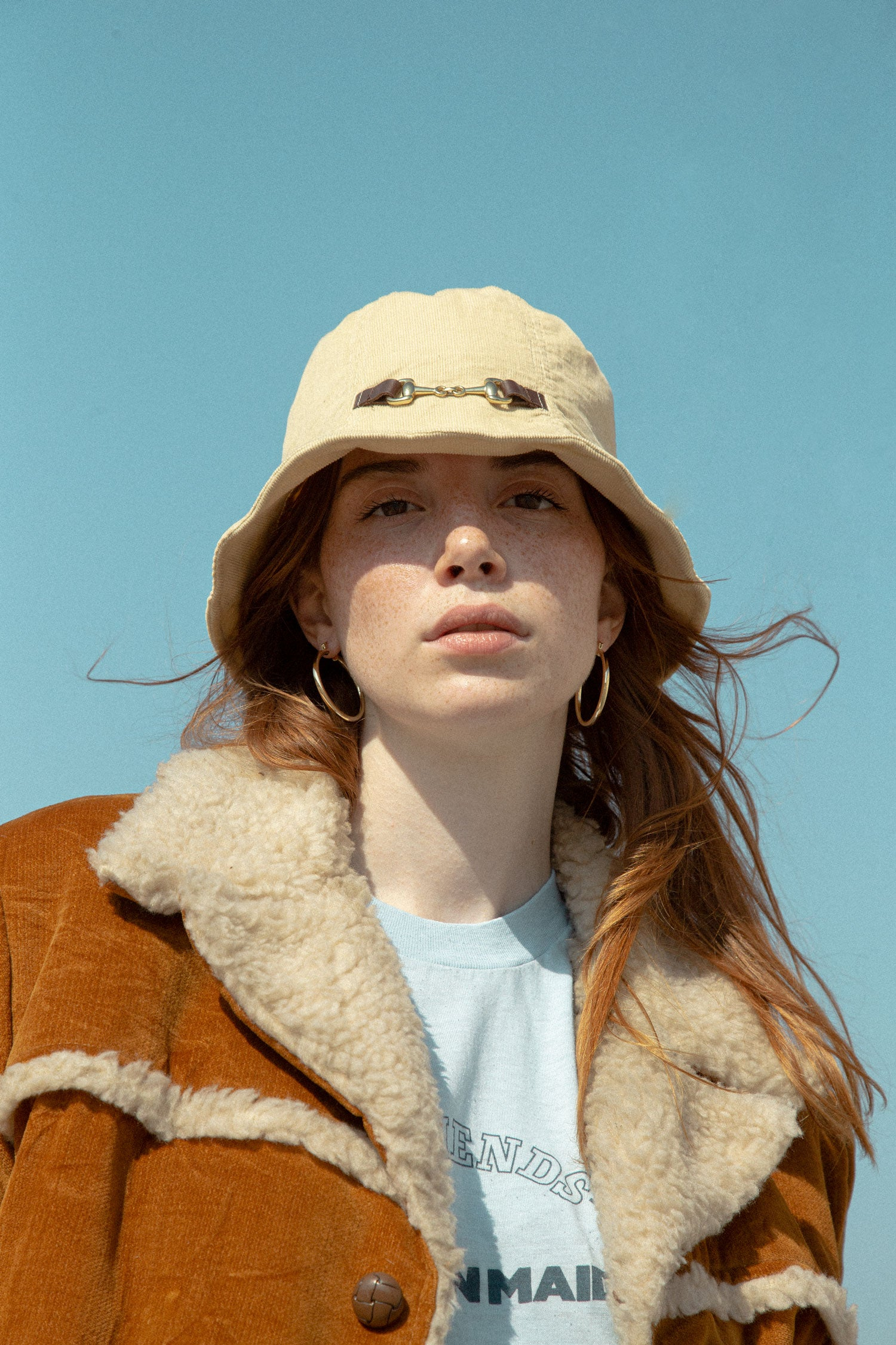 Model wearing vintage bucket hat, in front of blue sky.