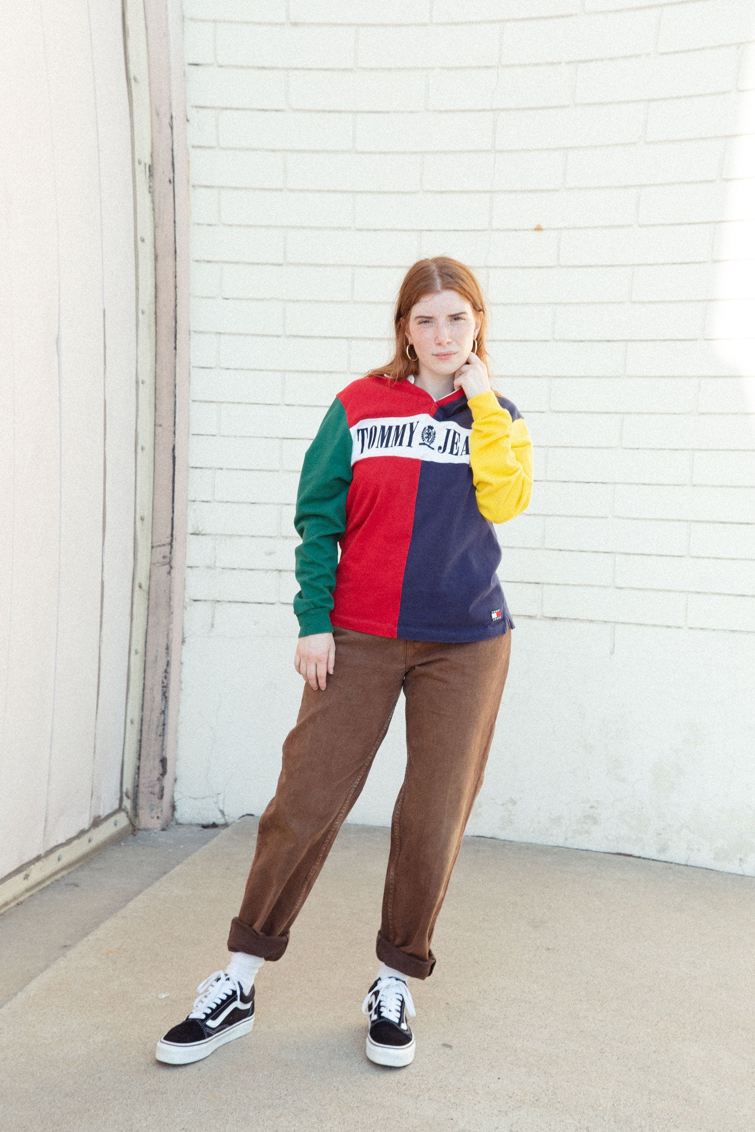 Female model standing on sidewalk against white brick wall, wearing Tommy Hilfiger 90s rugby top, and high waisted brown Levi's jeans.