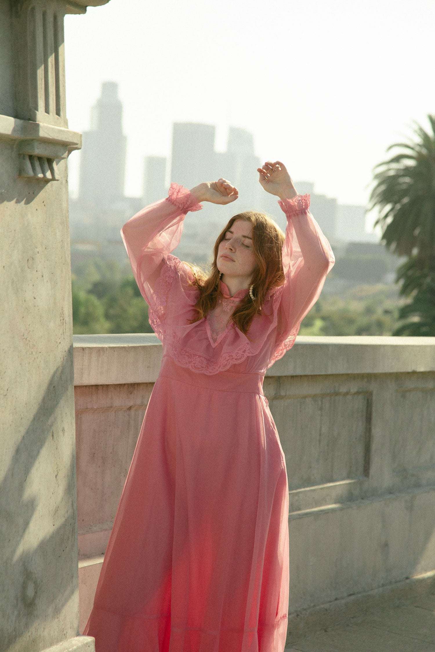 Woman standing on bridge with downtown Los Angeles in the background.  Wearing 80s prairie style, pink maxi dress.