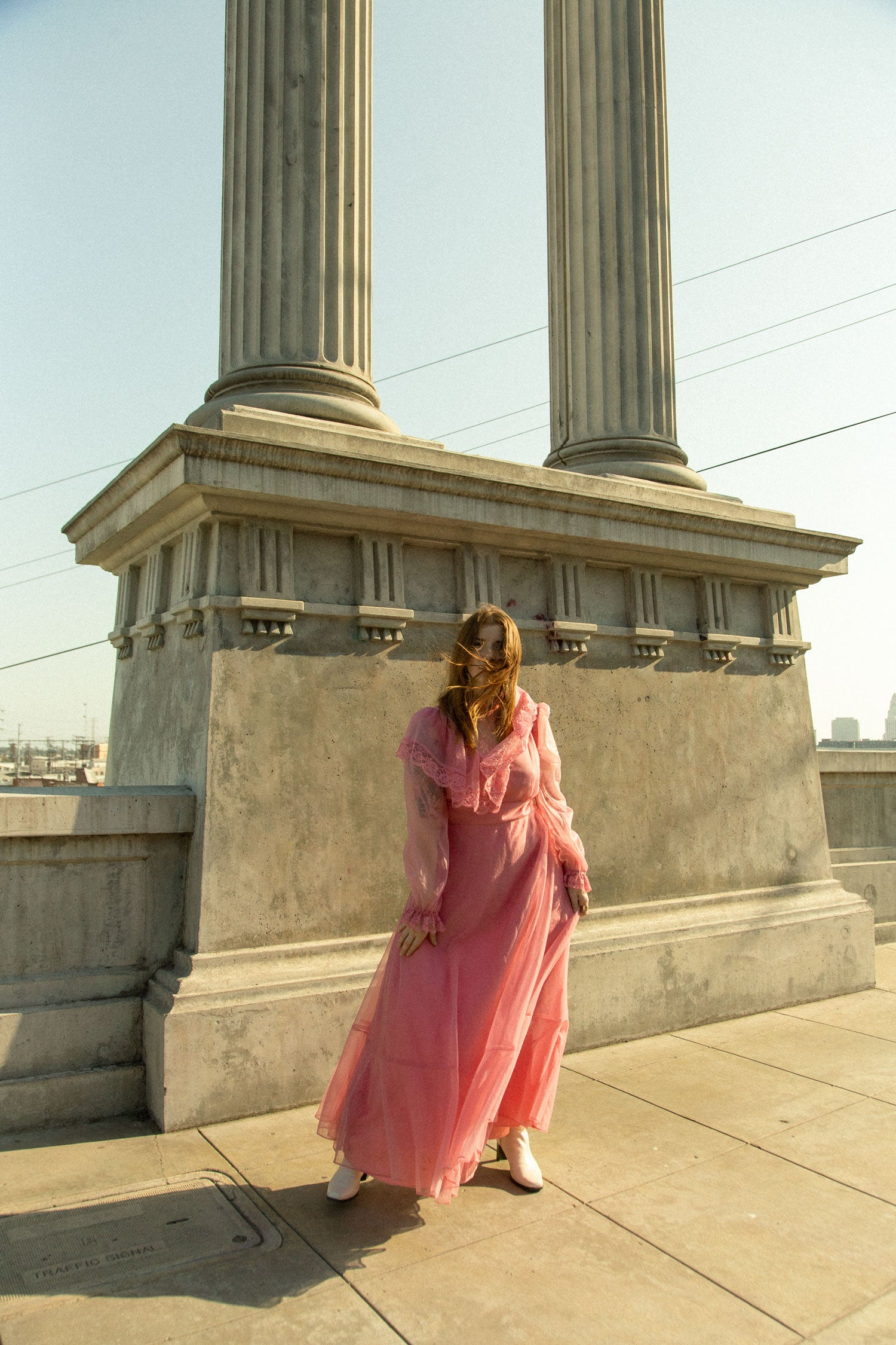 Woman standing on bridge, with wind blowing hair in face.  Wearing vintage 80s prairie style, pink maxi dress.